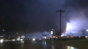 Driving east on Highway 66 in Rowlett, TX as a large and violent tornado strikes the town. Damage is along highway 66 including power substation explosions.
