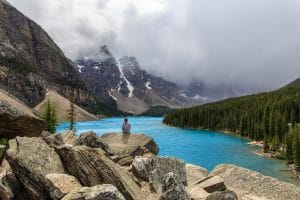 A lone girl sits on a pile of rocks overlooking Moraine Lake in Banff National Park