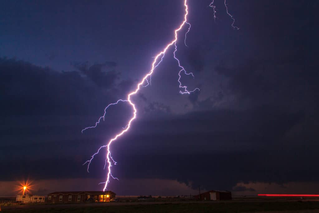 Lightning striking behind a house